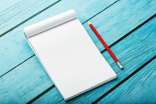 Bloco de notas com lápis vermelho sobre um fundo azul mesa de madeira, para educação, escrever metas e ações Foto Premium