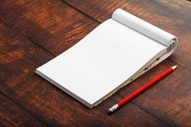 Bloco de notas com lápis vermelho sobre um fundo de mesa de ...