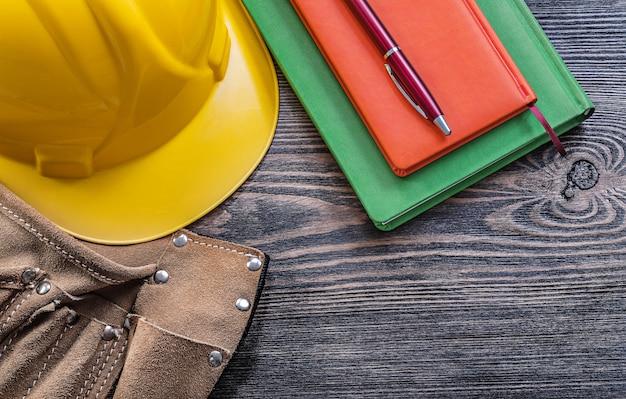 Bloco de notas de cinto de ferramentas de couro caneta capacete protetor no conceito de construção de tábua de madeira Foto Premium