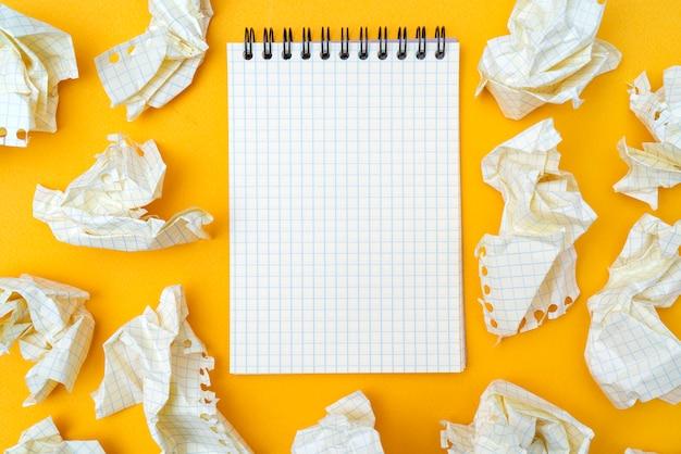 Bloco de notas e folhas de papel amarrotadas em um fundo amarelo. Foto Premium