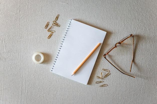 Bloco de notas e lápis sobre um fundo cinza. Foto Premium