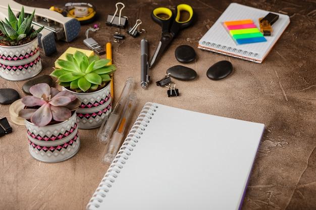 Bloco de notas e suculentas na mesa. o conceito de negócio. Foto Premium
