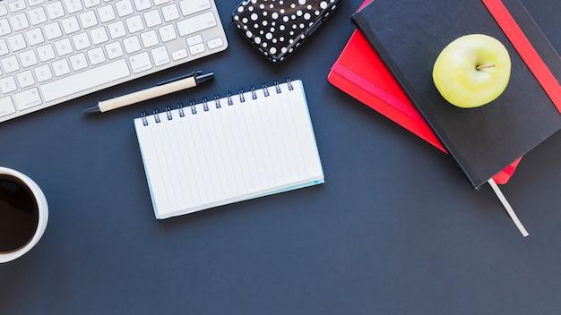 Bloco de notas e teclado perto da xícara de café e maçã Foto gratuita