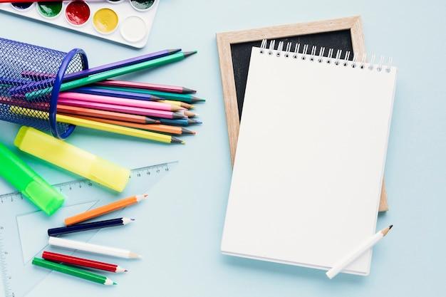 Bloco de notas em branco ao lado de lápis de cor Foto gratuita