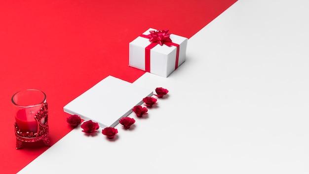 Bloco de notas em branco com pequenos botões de rosas na mesa Foto gratuita