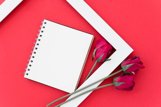 Bloco de notas em branco com rosas vermelhas no quadro Foto gratuita
