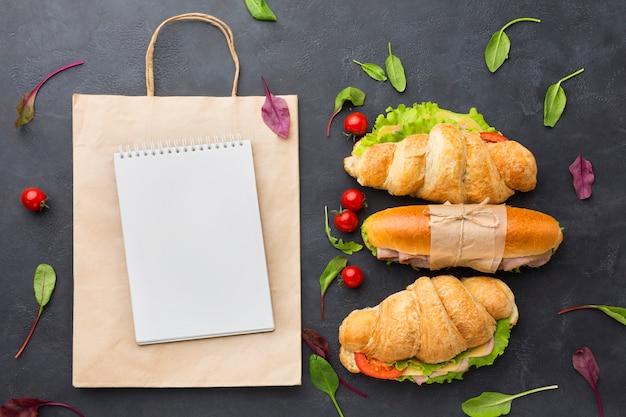 Bloco de notas em branco e sanduíches saudáveis Foto gratuita
