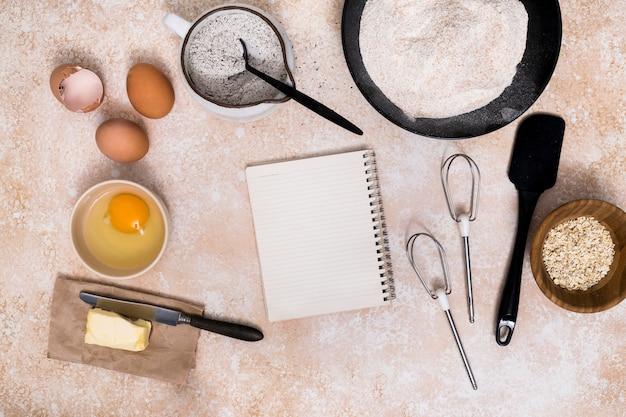 Bloco de notas em branco espiral com ingredientes pão no plano de fundo texturizado Foto gratuita