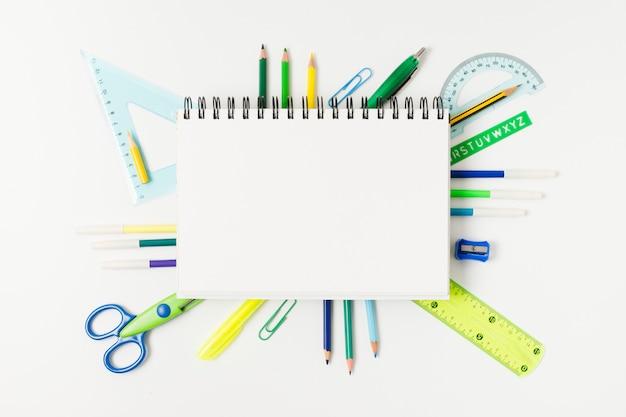Bloco de notas em branco, rodeado por material de mesa Foto gratuita
