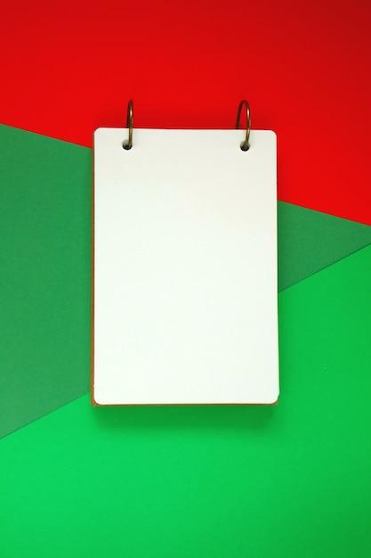 Bloco de notas em branco sobre fundo brilhante verde vermelho. caderno sobre fundo gráfico de tendência. configuração plana, vista superior, cópia espaço Foto Premium
