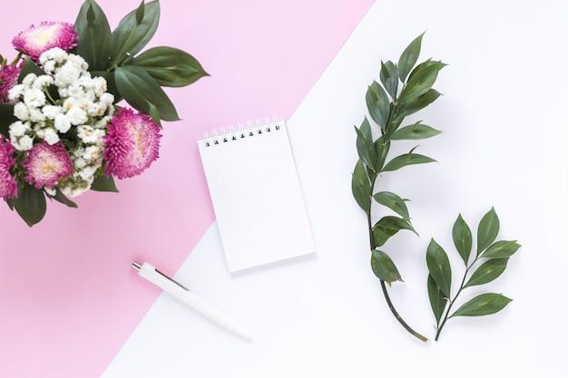 Bloco de notas em espiral; caneta; folhas e ramo de flores em fundo duplo Foto gratuita