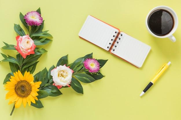 Bloco de notas em espiral; chá preto; caneta e flores em fundo colorido Foto gratuita