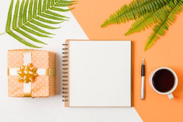 Bloco de notas em espiral com caneta; caixa de presente laranja e chá preto perto de folhas verdes sobre superfície dupla Foto gratuita
