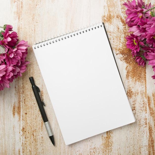 Bloco de notas em espiral com caneta e flores cor de rosa no plano de fundo texturizado de madeira Foto gratuita