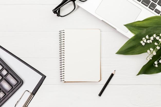Bloco de notas em espiral com lápis, calculadora, prancheta, óculos e laptop na mesa branca Foto gratuita