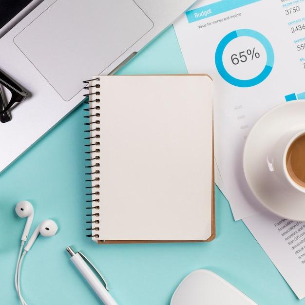 Bloco de notas em espiral fechado com laptop, fone de ouvido, caneta, mouse e xícara de café no plano de orçamento na mesa azul Foto gratuita