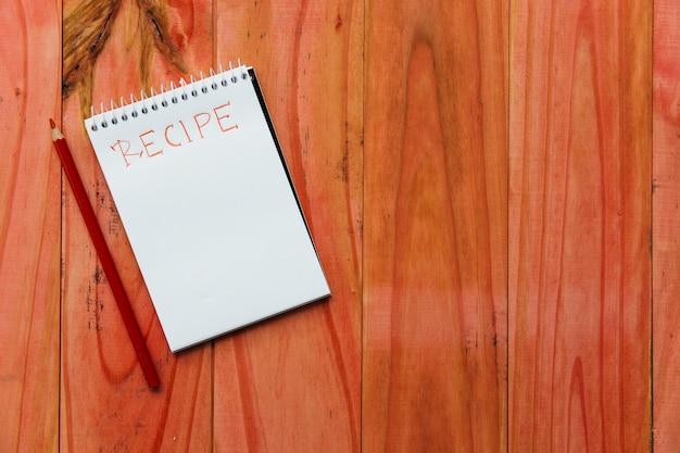 Bloco de notas em espiral perto de palavra receita perto de lápis em fundo de madeira Foto gratuita