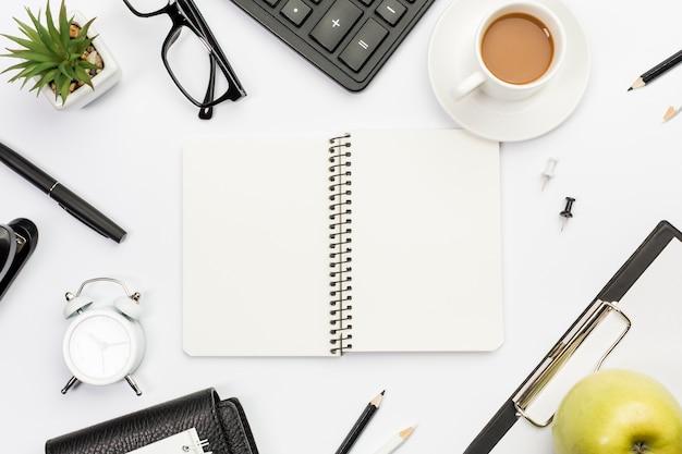 Bloco de notas em espiral rodeado com artigos de papelaria, maçã e café na mesa de escritório branco Foto gratuita