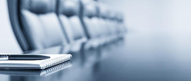 Bloco de notas em uma mesa com caneta antes de conhecer, tom azul, conceito do negócio com espaço de cópia Foto Premium
