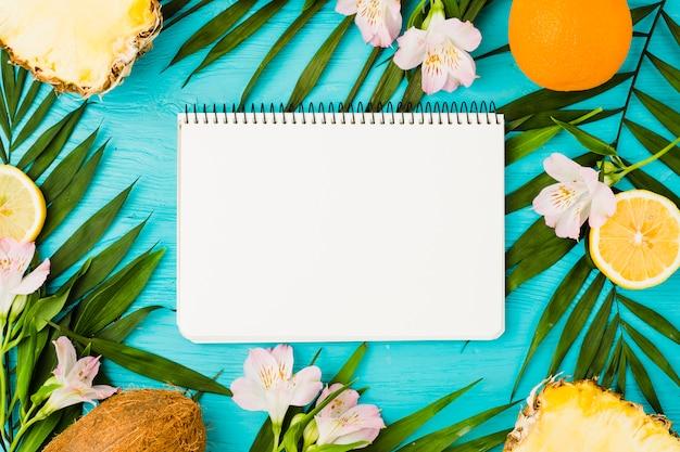 Bloco de notas entre folhas de plantas e frutas perto de flores Foto gratuita