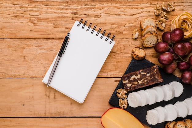 Bloco de notas espiral em branco com caneta esferográfica perto de ingredientes crus sobre o plano de fundo texturizado Foto gratuita