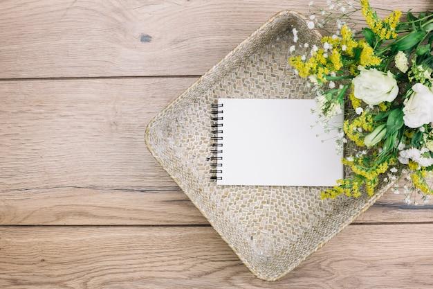 Bloco de notas espiral em branco e buquê de flores frescas na cesta na mesa de madeira Foto gratuita