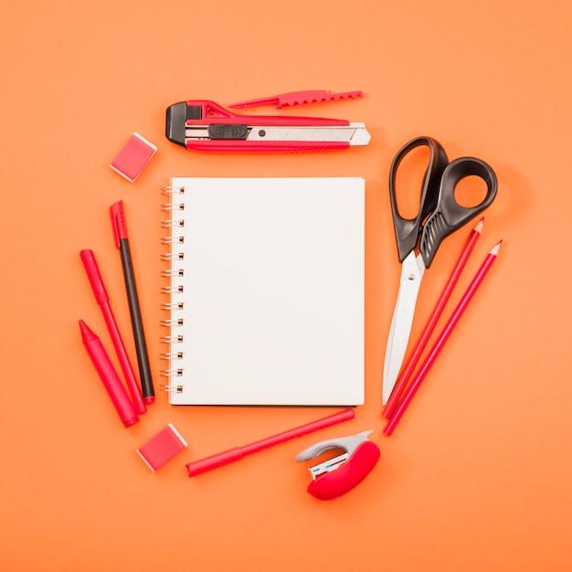 Bloco de notas espiral em branco e tesoura com artigos de papelaria sobre fundo laranja brilhante Foto gratuita