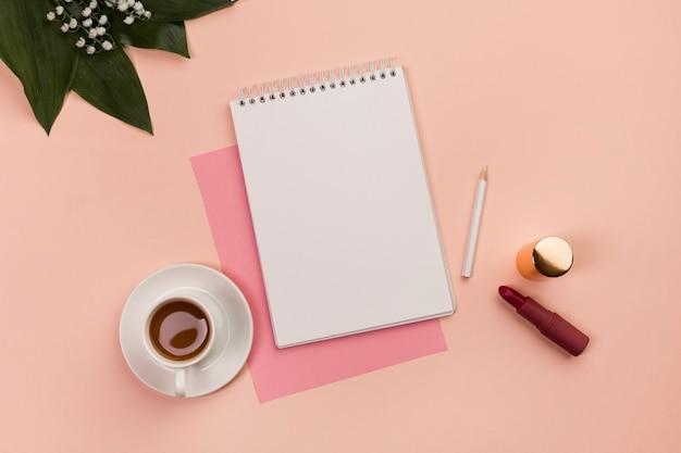 Bloco de notas espiral em branco, lápis, batom, xícara de café e folhas no fundo pêssego Foto gratuita