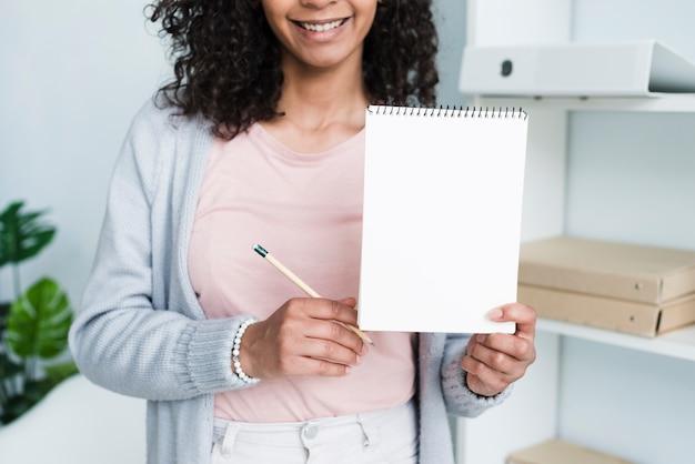 Bloco de notas mostrando fêmea alegre novo Foto gratuita