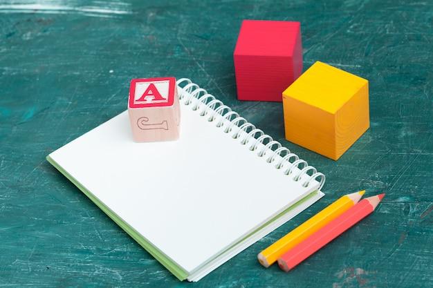 Bloco de notas na mesa de madeira e blocos de madeira alfabeto Foto Premium