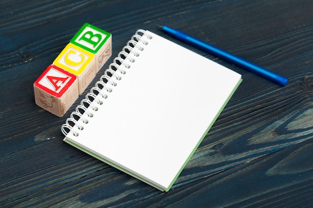 Bloco de notas na mesa de madeira e blocos de madeira com alfabeto Foto Premium