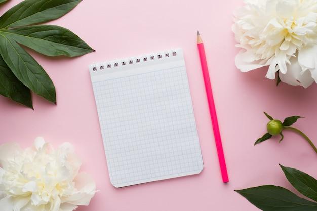 Bloco de notas para a peônia das flores brancas do texto no fundo do rosa pastel. Foto Premium