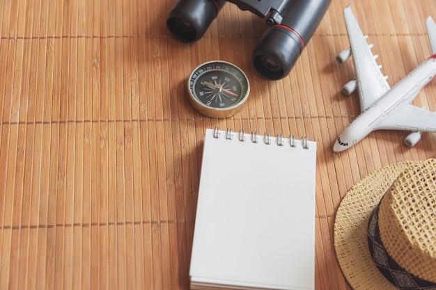 Bloco de notas para nota com passaporte, binóculos, lápis, bússola, avião no mapa de papel para imagem de descoberta de aventura de viagem Foto Premium