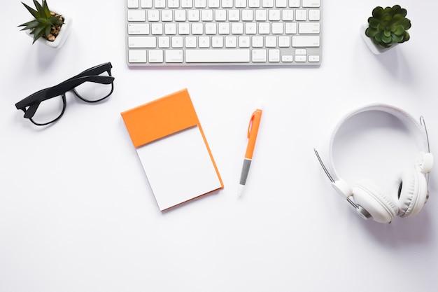 Bloco de notas pegajoso em branco; óculos; caneta; cactos; fone de ouvido e teclado na mesa branca Foto gratuita