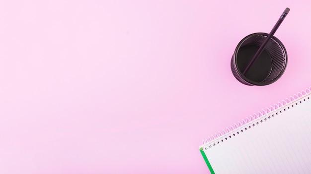 Bloco de notas perto de copo plástico com lápis no fundo rosa Foto gratuita