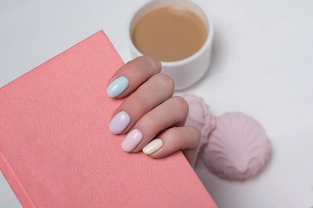 Bloco de notas rosa em uma mão feminina. manicure suave. fechar-se Foto Premium