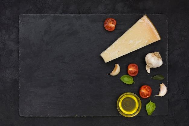 Bloco de queijo; dentes de alho; manjericão e tomates cortados ao meio com azeite de oliva na pedra ardósia sobre o fundo preto Foto gratuita