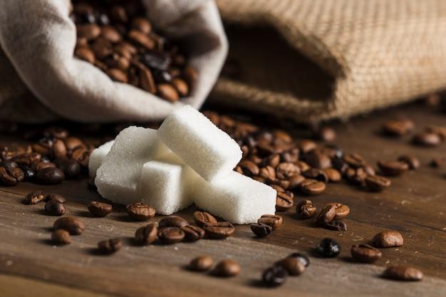 Blocos de açúcar e saco com grãos de café Foto gratuita