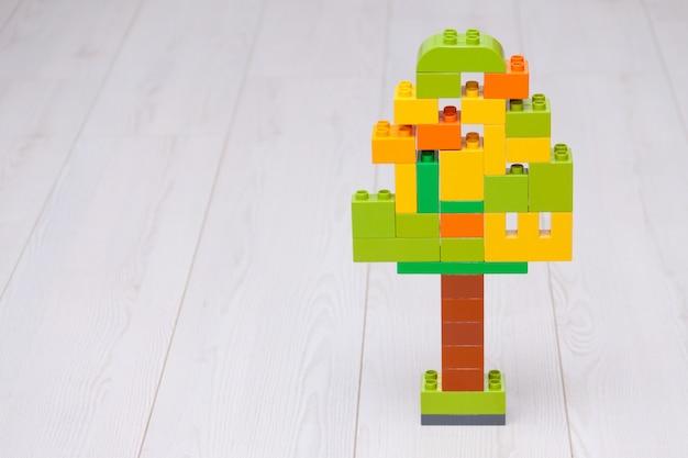 Blocos de apartamentos plásticos coloridos na forma da árvore no fundo claro. Foto Premium