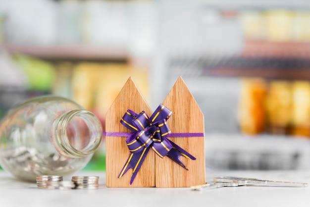 Blocos de casas de madeira amarradas com laço de fita com moedas e chaves na mesa branca Foto gratuita