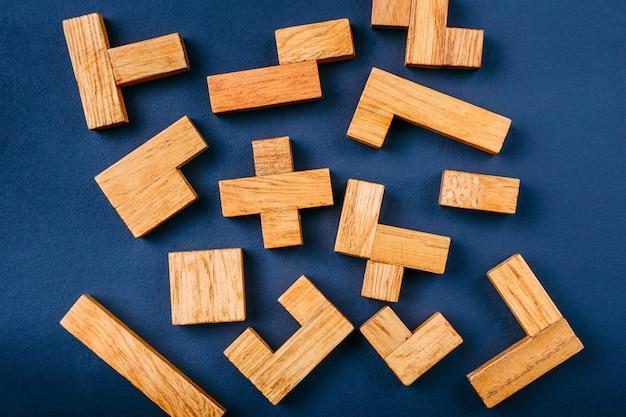 Blocos de madeira das formas geométricas diferentes em um fundo escuro. Foto Premium