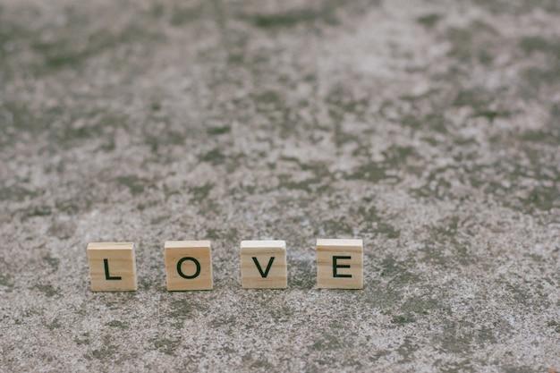 Blocos de madeira de texto soletrando a palavra amor no plano de fundo texturizado concreto Foto Premium