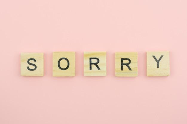 Blocos de madeira de texto soletrando a palavra desculpe no fundo rosa Foto Premium