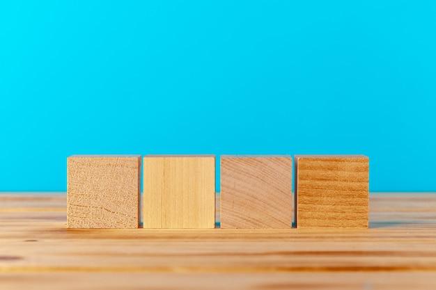 Blocos de madeira na mesa de madeira contra um fundo azul, copie o espaço Foto Premium