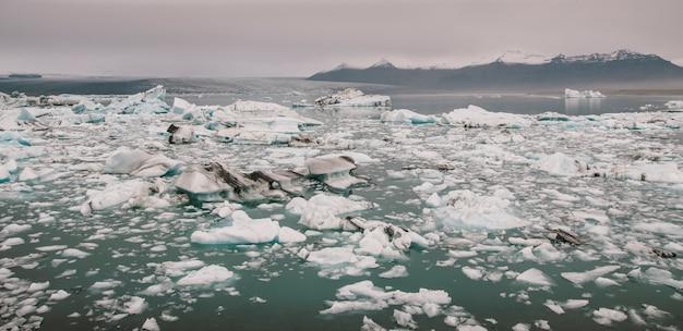Blocos enormes de gelo no rio glacial e iceberg azuis no lago da geleira de jokulsarlon. Foto Premium