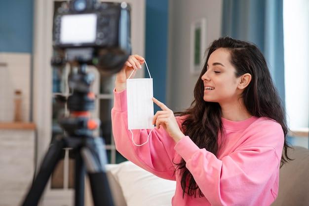 Blogger, apontando para a máscara cirúrgica na frente da câmera Foto gratuita