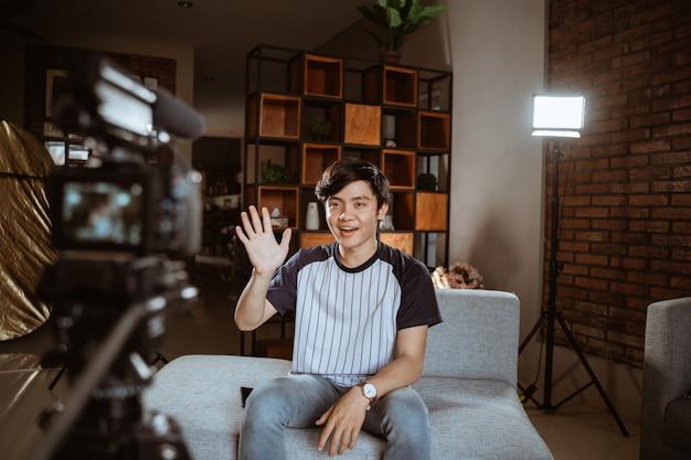 Blogger asiático jovem gravação vlog falando com a câmera Foto Premium