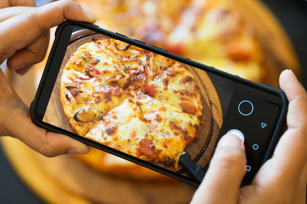 Blogger de comida tirando foto de pizza cozida. Foto Premium