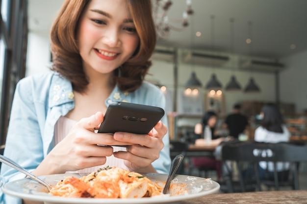Blogger feminino fotografando o almoço no restaurante com o telefone dela Foto gratuita