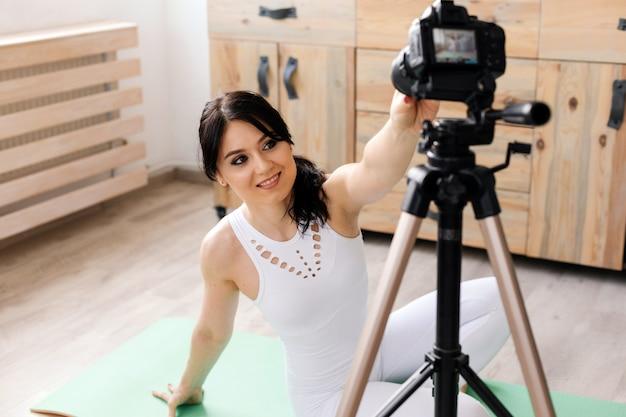 Blogger feminino jovem, gravando vídeo de esportes em casa Foto Premium